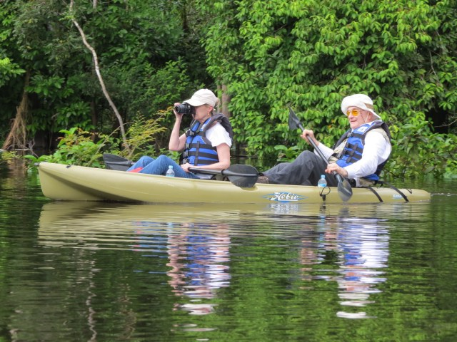 A man and woman in a kayak, he is padding, she is looking through binoculars