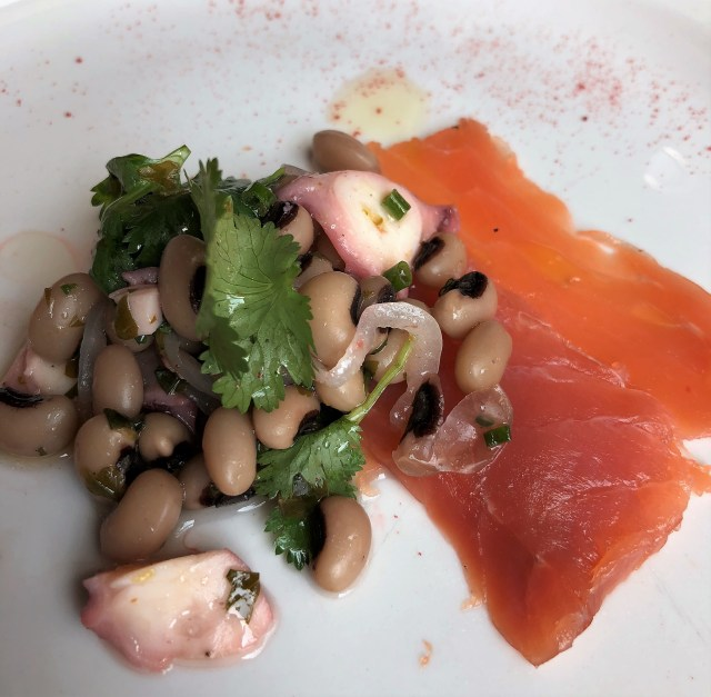 A plate of octopus ceviche with a slice of smoked salmon
