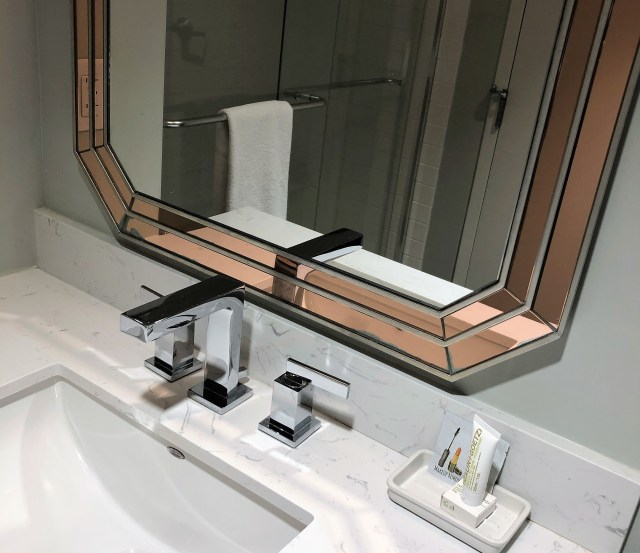 Closeup/partial of white bathroom sink and vanity, silver faucets, bottom of mirror framed in pink-tinted glass