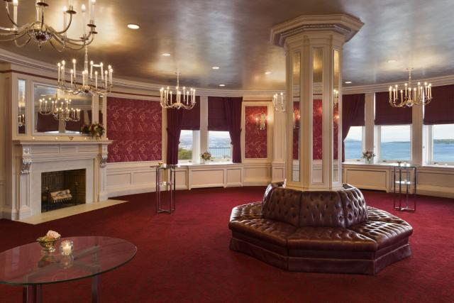 A meeting room with cranberry carpet, wallpaper and leather seating around a mirrored column, silver ceiling, crystal chandeliers and white woodwork.