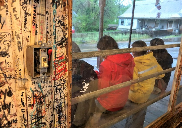 Through a window, the backs of four restaurant patrons wait to be seated