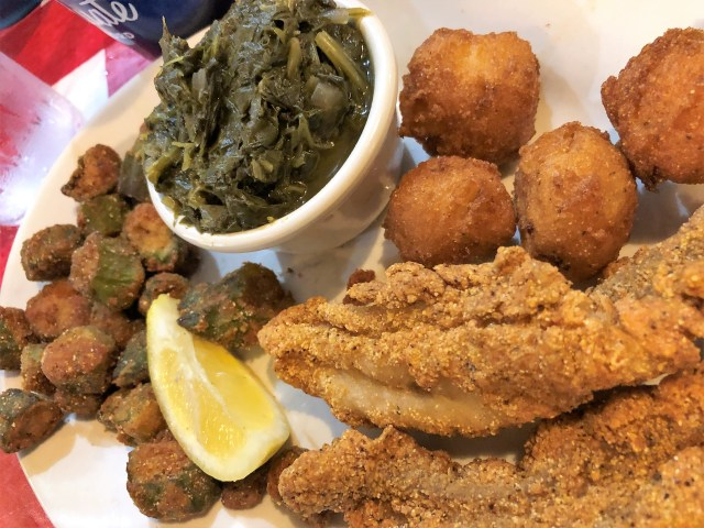 A white dinner plate piled with fried catfish, hush puppies, fried okra, cooked greens and a lemon wedge