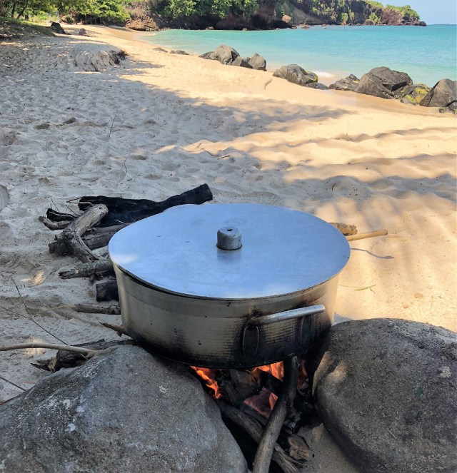A silver dutch oven sits on a fire on a sandy beach, ocean in the background