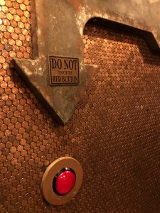 A wall lined with copper pennies, an arrow points to a red button, the sign says do not touch the red button