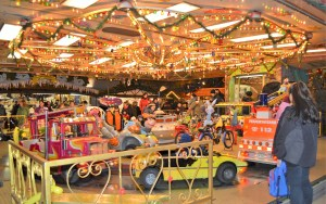 An outdoor carousel ride with brightly colored cars and overhead lights