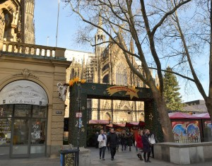 An arch at the entrance to a Christmas market, a cathedral in the background