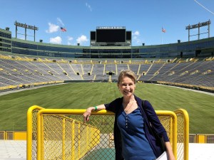 The author stands in front of an empty football field and stadium