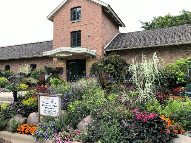 A brick low-rise building with flower-and-rock garden in front