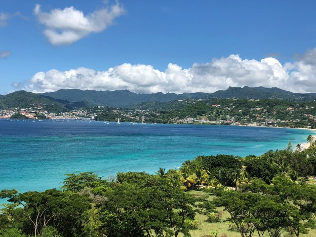 Grand Anse Bay with landscaped park in front and mountains in the background
