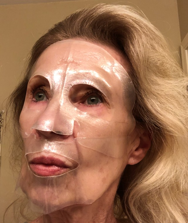 The face of a woman (me) with blond hair and her face covered with a sheer plastic-like mask