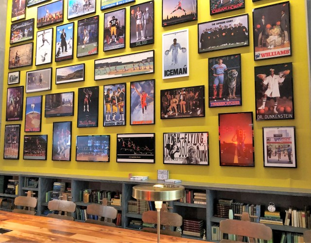 About 3 dozen framed sports posters hang on a yellow wall