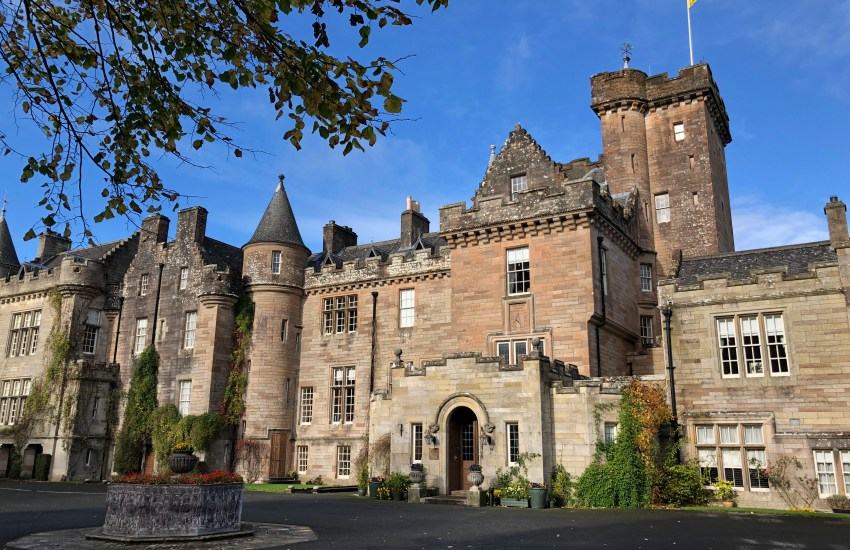 An elongated stone castle with towers, turrets and crenellations,