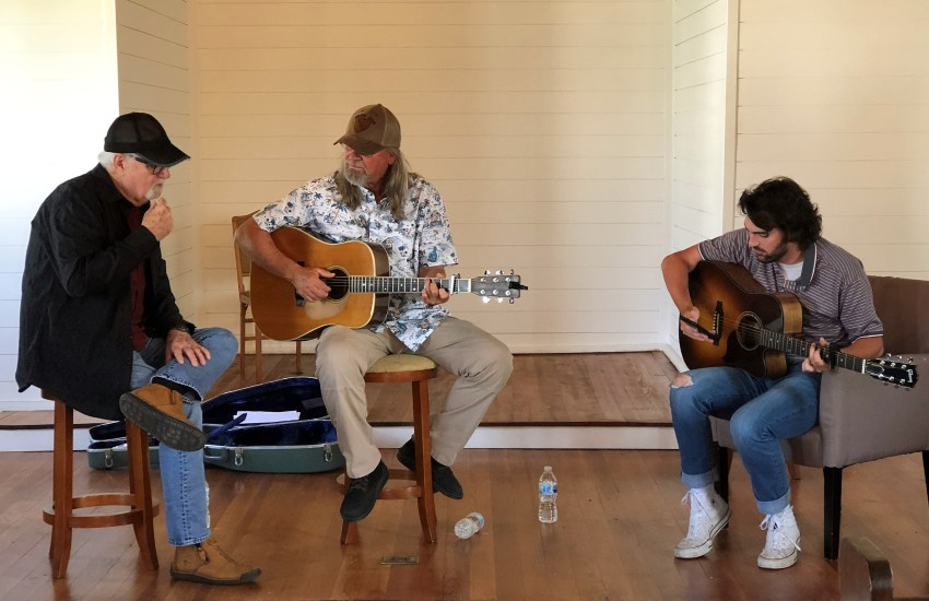 Three men on a stage in casual apparel, two with guitars.