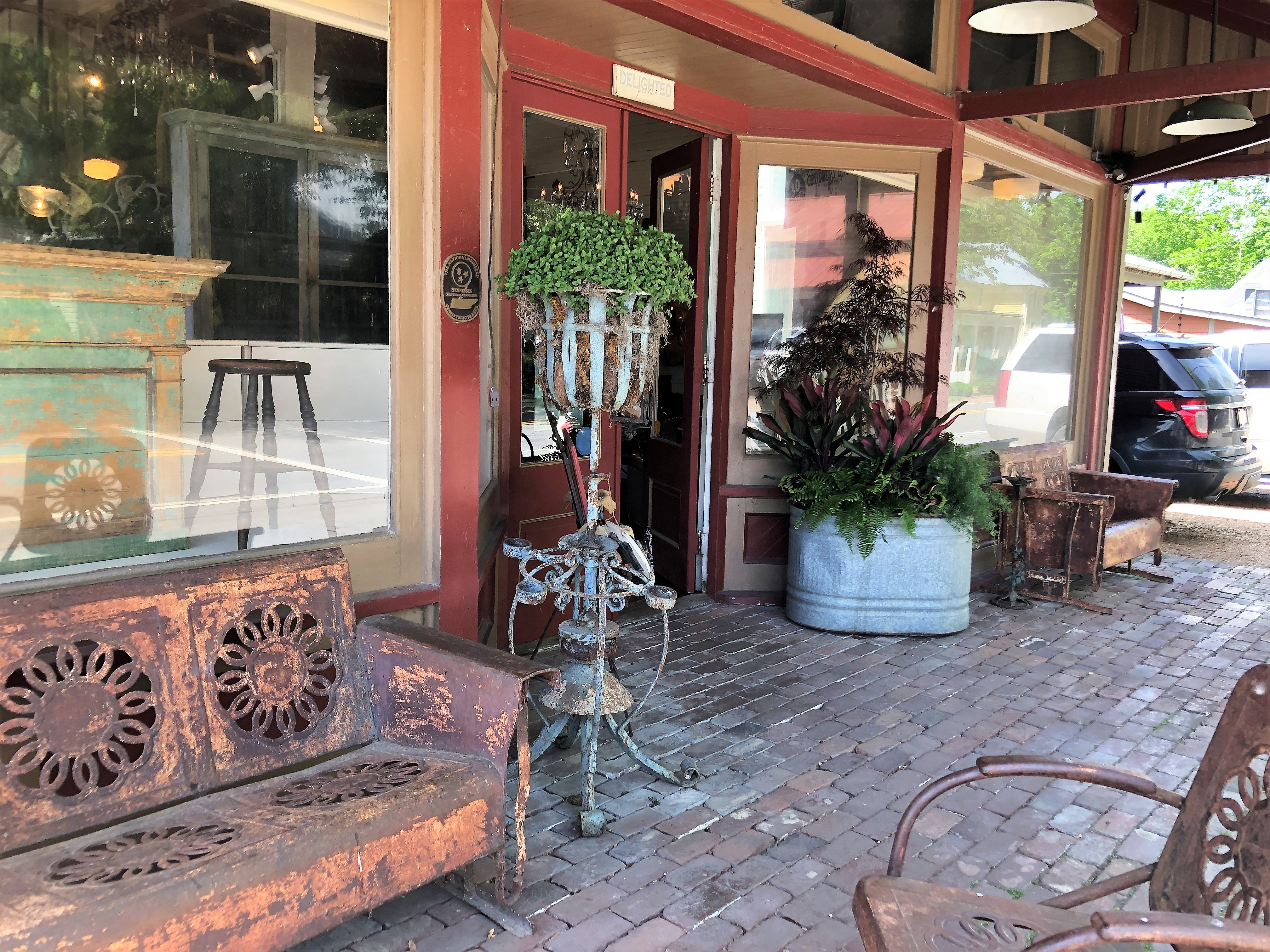 The front of an antique store has large glass windows and a brick sidewalk. On display are rusty garden furniture and plant stands.