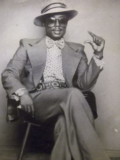 A man in the funky styles of the 70s, wear bell bottom pants, jacket and hat