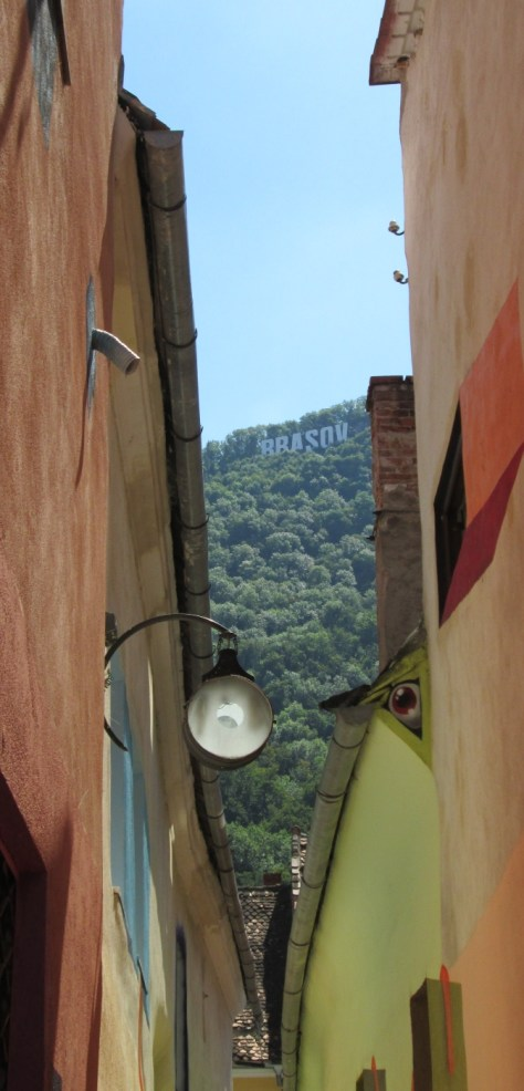 """Eye"" street light on Rope Street, Strada Sforii, and the Hollywood-style 'Braşov' sign up on the mountain. Image by @PatFurstenberg"