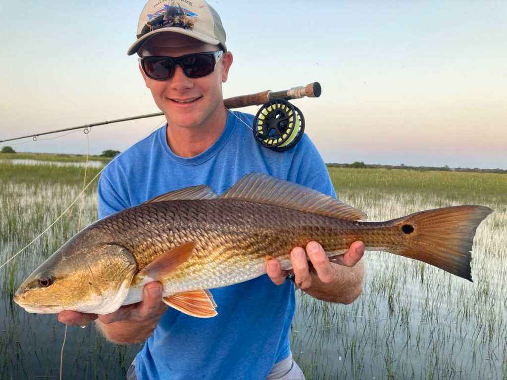 Man holding redfish caught with Lamson Liquid fly reel resting over his shoulders.