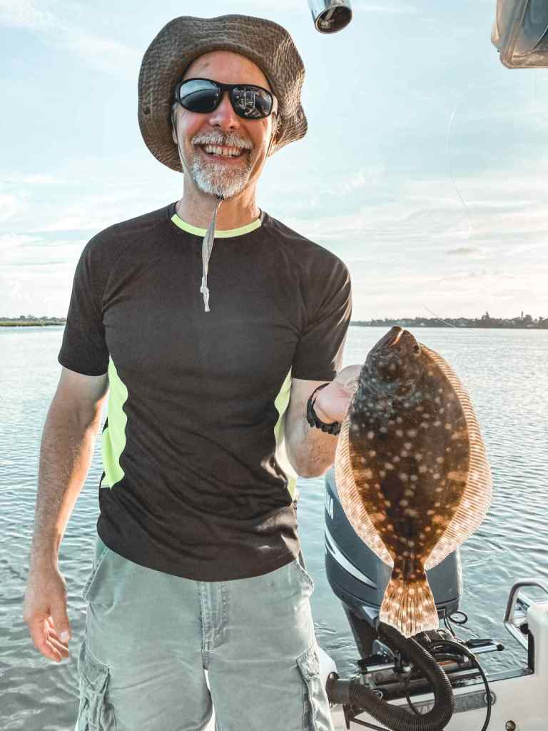 Man holding flounder up on the water.