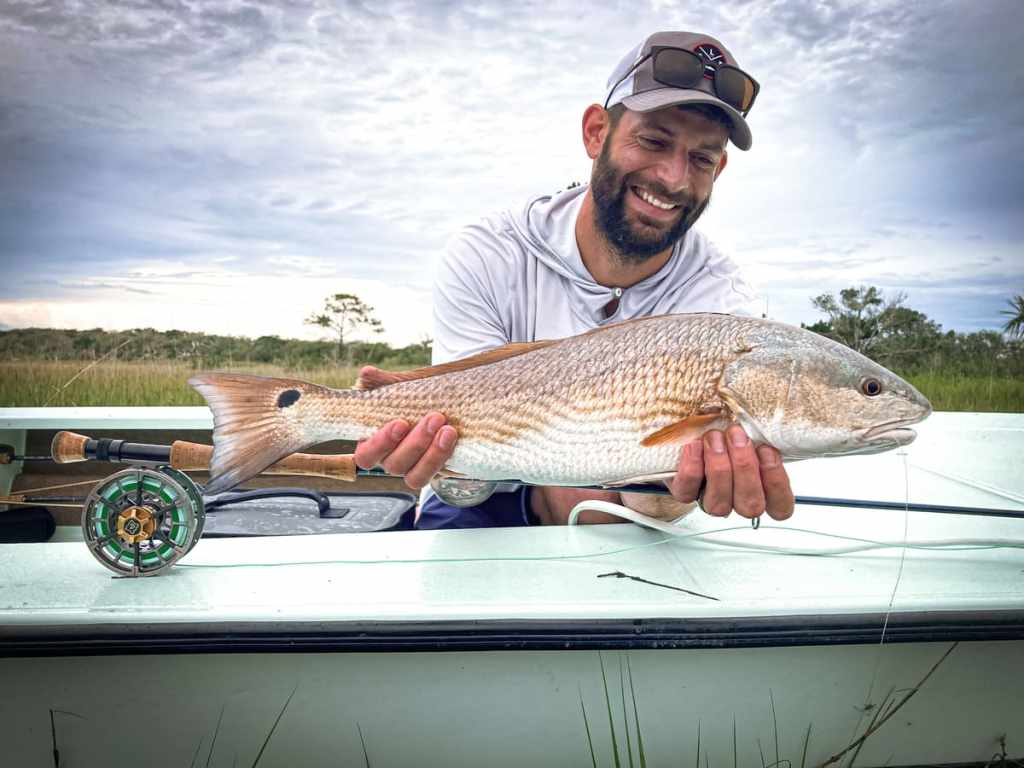 Fly reel on boat while man poses with redfish.