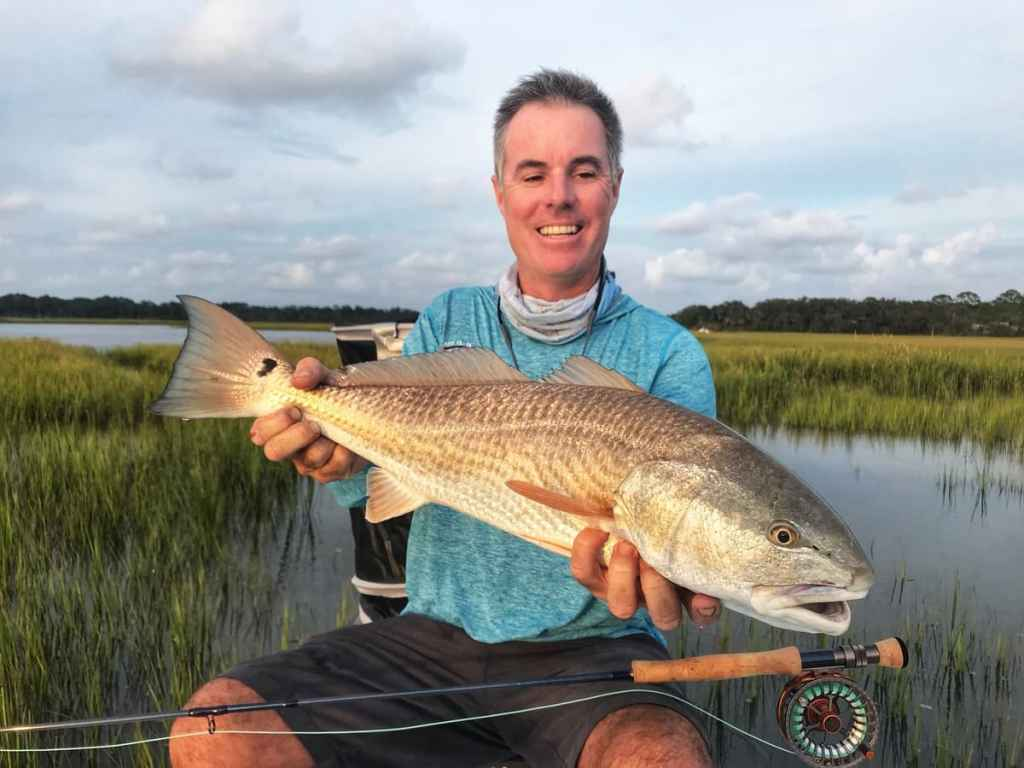 Man catches redfish using sealed drum disc drag fly reel