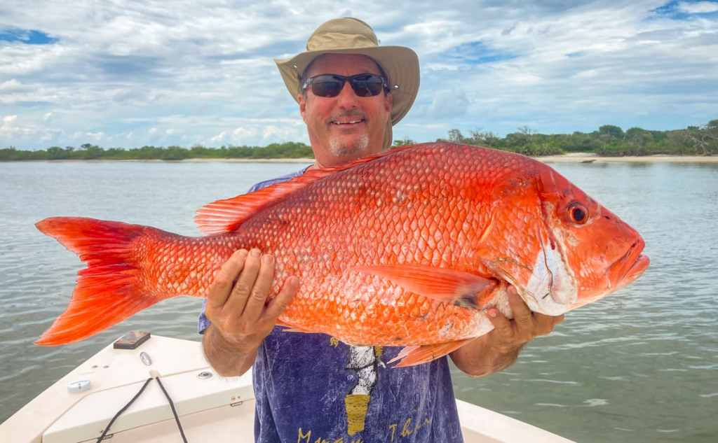 Man holding snapper caught while booking a charter.