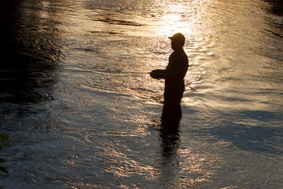 Man fishing in river looks like shadow casting.