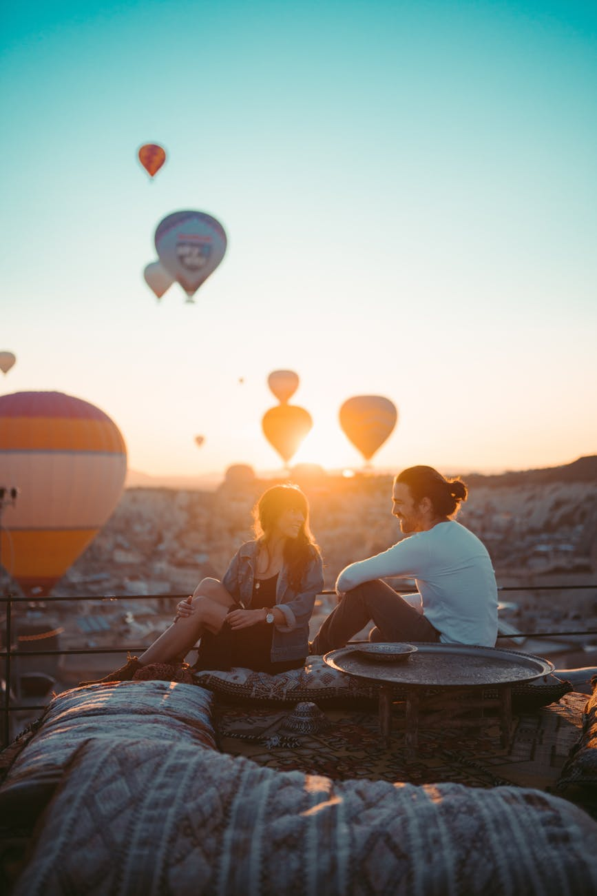 people sitting on rooftop during sunset