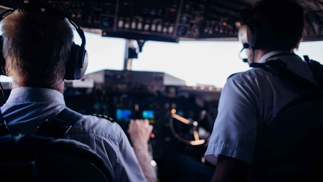 pilots operating airplane in cockpit during flight