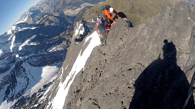 Alastair Macartney stood on the back of the north face of the Eiger preparing to bASE jump from it in his wingsuit.  Photo by Chris