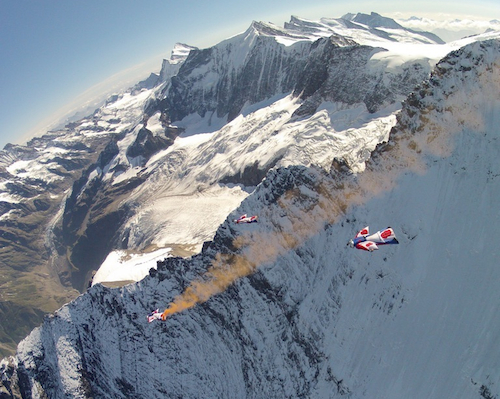 """Photo by Chris """"Douggs"""" McDougall showing Alastair Macartney and the Jump4Heroes team building an arrowhead human flight wingsuit formation as they fly past the east ridge of the Eiger."""