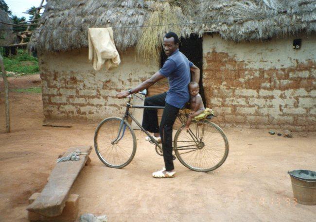 Baa bikes around compound, holding Sassandra behind him on wheel, 8-13-93