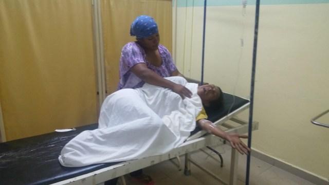 Rosa María Martínez madre de los dos muertos y el herido y esposa del motoconchista mientras es auxiliada por un pariente en el Hospital Toribio Pascasio en Salcedo. (Foto: FE)