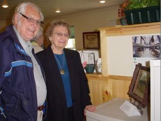 #11b Lorna and Don Brink stand by the photo of Don's grandfather, Almond Civil War Vet