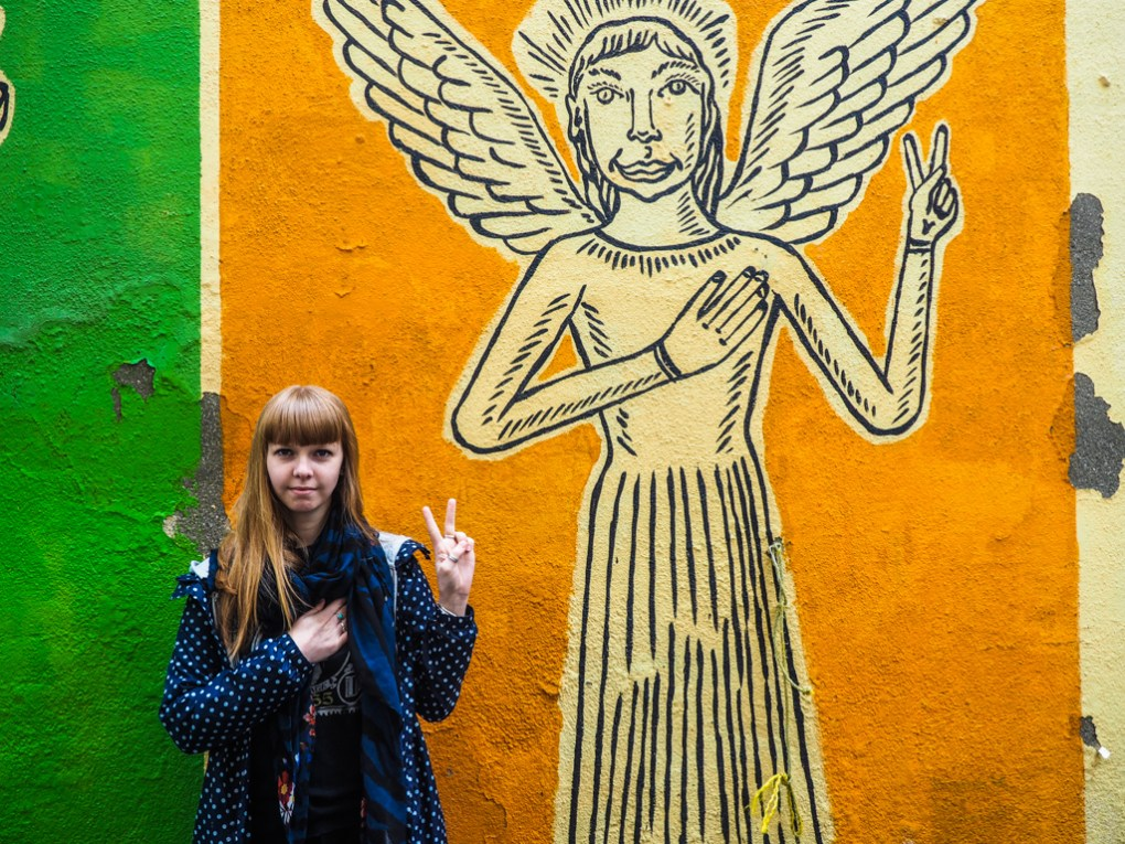 Almost Ginger blog owner posing with street art in Lisbon, Portugal