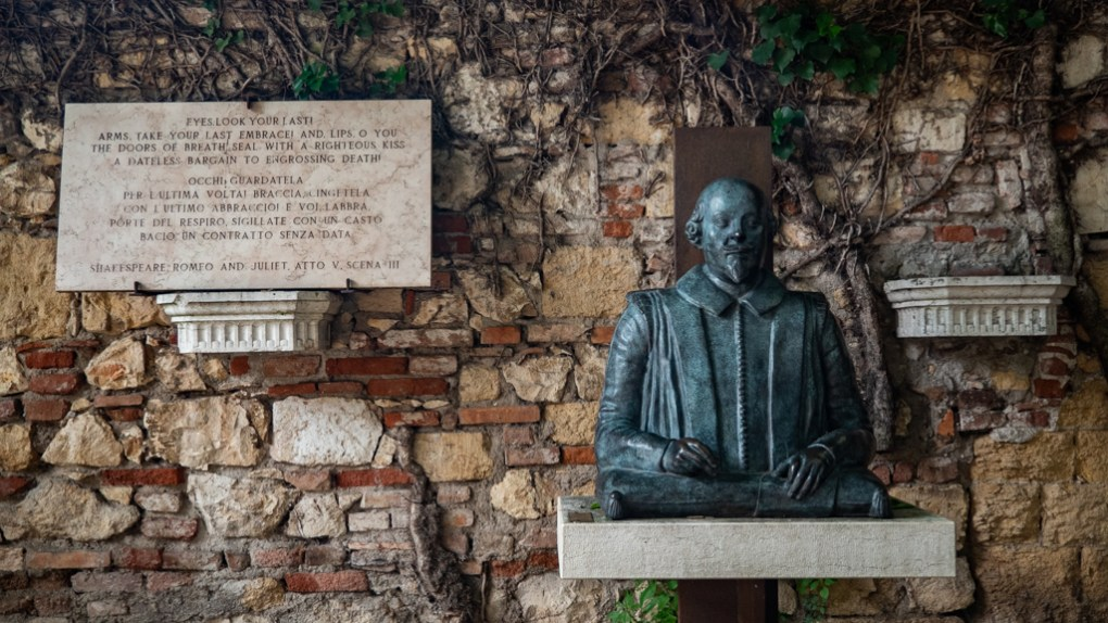 Plaque of Romeo and Juliet play excerpt and William Shakespeare bust at Juliet's Tomb in Verona, Italy