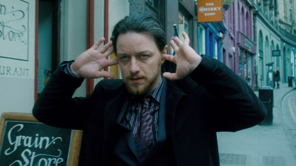 James McAvoy walking down Victoria Street in Edinburgh with his fingers in his ears in the film Filth (2013)
