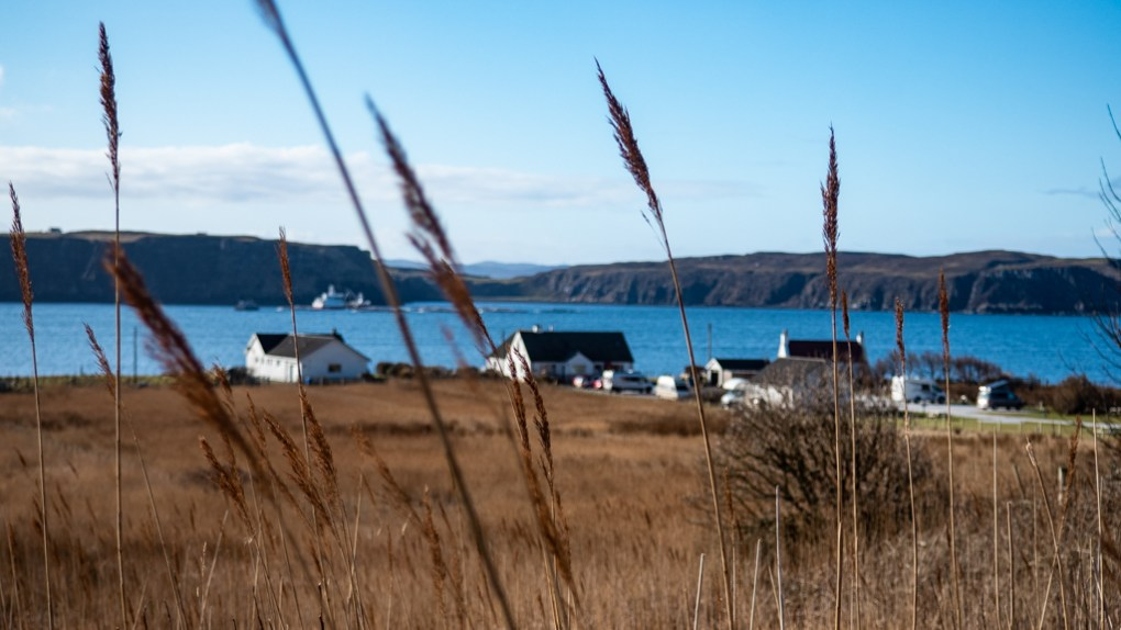 Uig through long grass on the Isle of Skye, Scotland