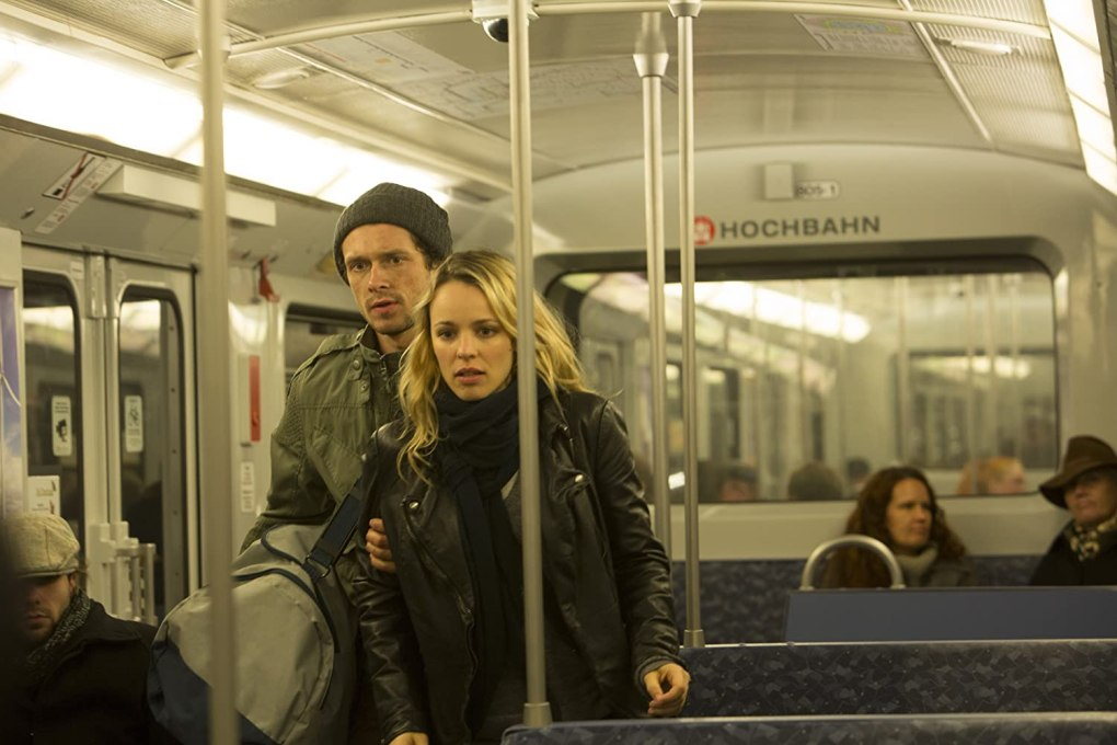 Film still from A Most Wanted Man (2014) of a man and woman stood on a metro train