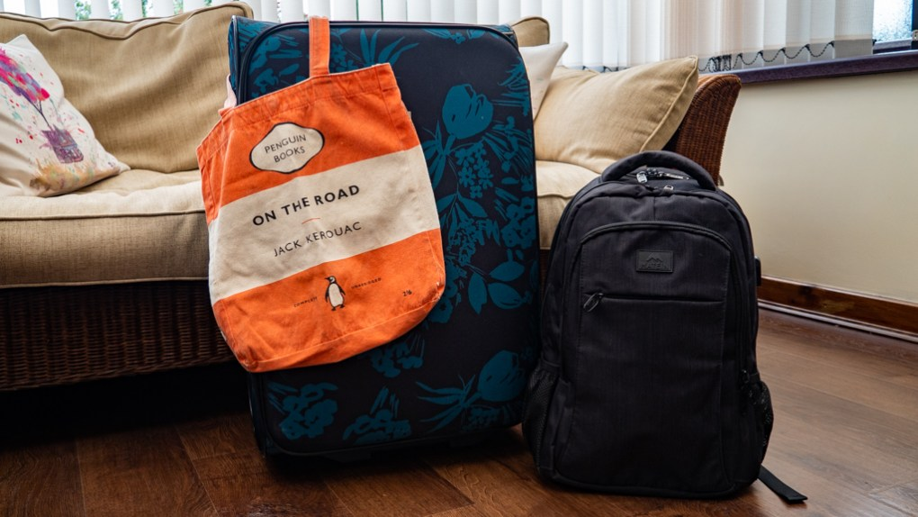 Teal flowery suitcase, black backpack and Penguin tote bag