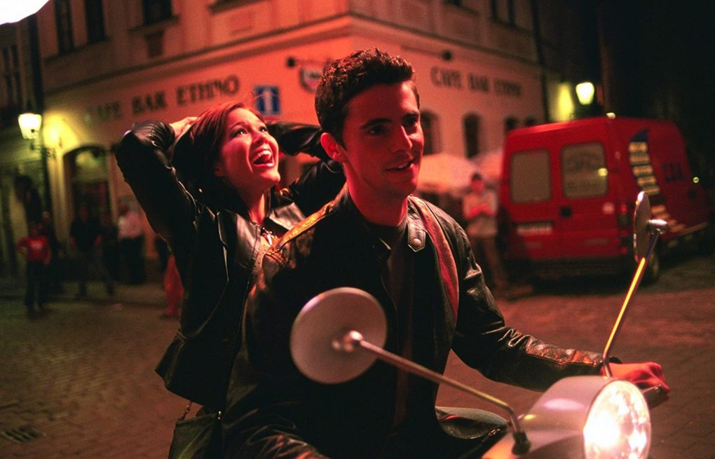 Chasing Liberty (2004) film still of Mandy Moore riding on the back of Michael Goode's vespa in Venice, Italy