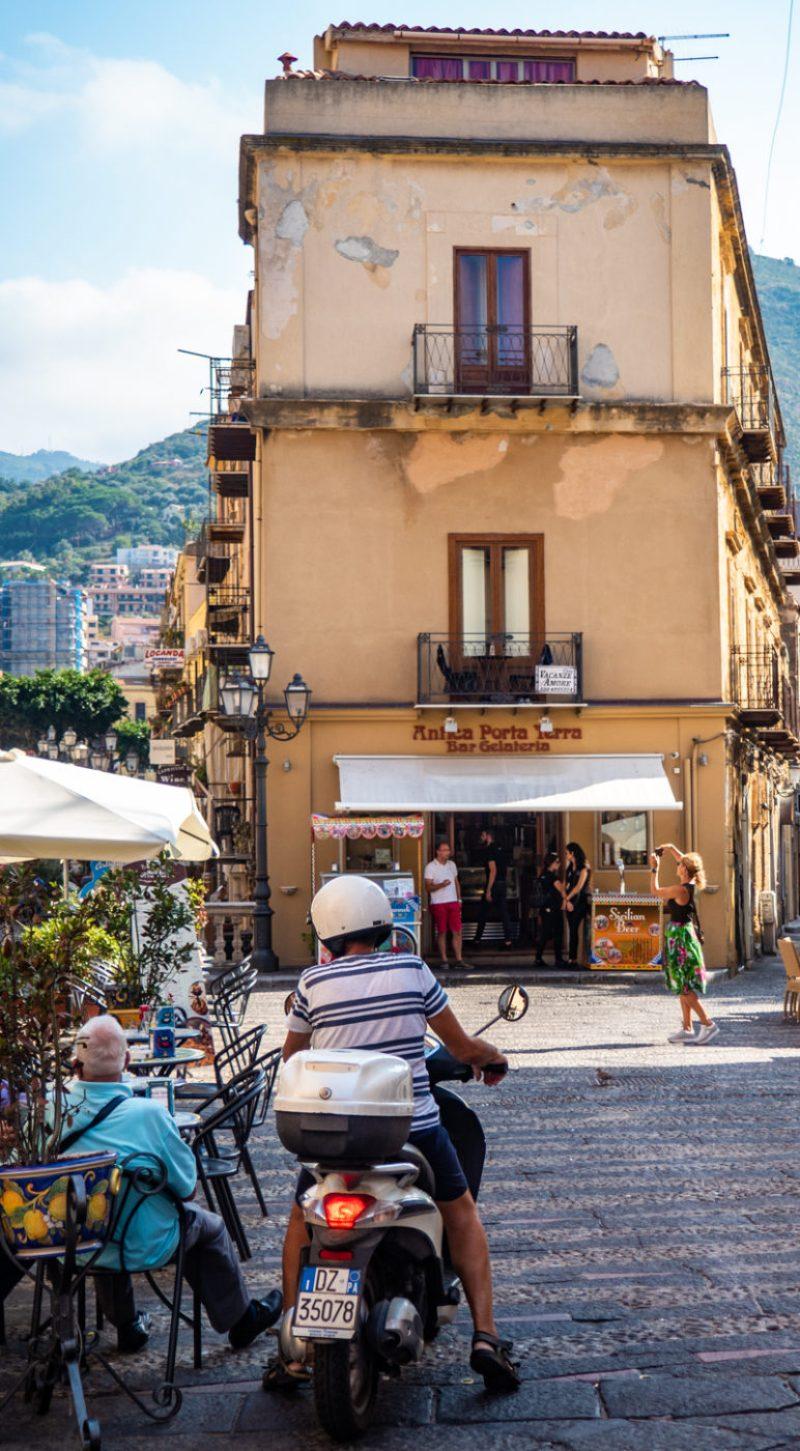 Man on a motorbike in front of Antica Porta Terra in Cefalù, Sicily