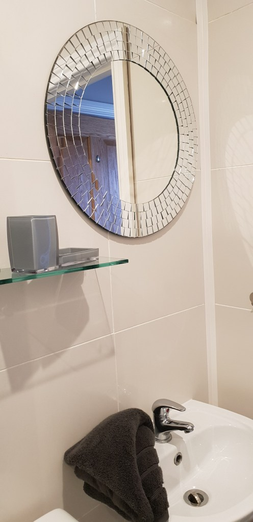 Bathroom sink and mirror in upstairs shower room