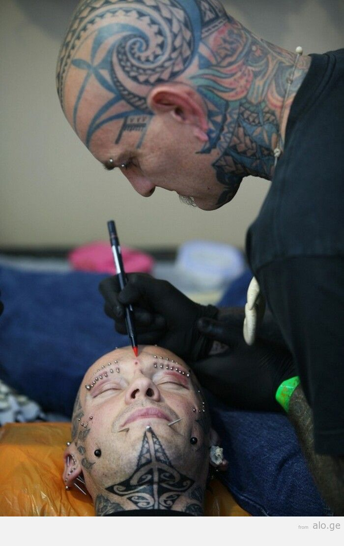 A tattoo artist (R) works at the fifth i
