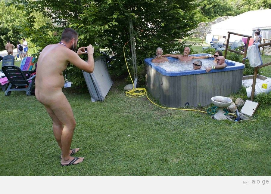 """A man takes a picture of friends during the """"www.inudisti.it"""" web community's annual gathering on private property at Oasis of Zello naturist resort near Bologna"""