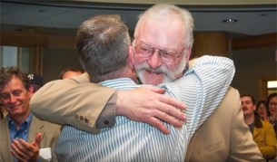 Man giving another a congratulatory hug