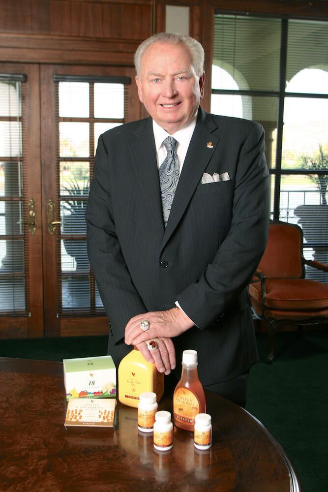 Rex Maughan stoji pokraj nekoliko proizvoda na stolu