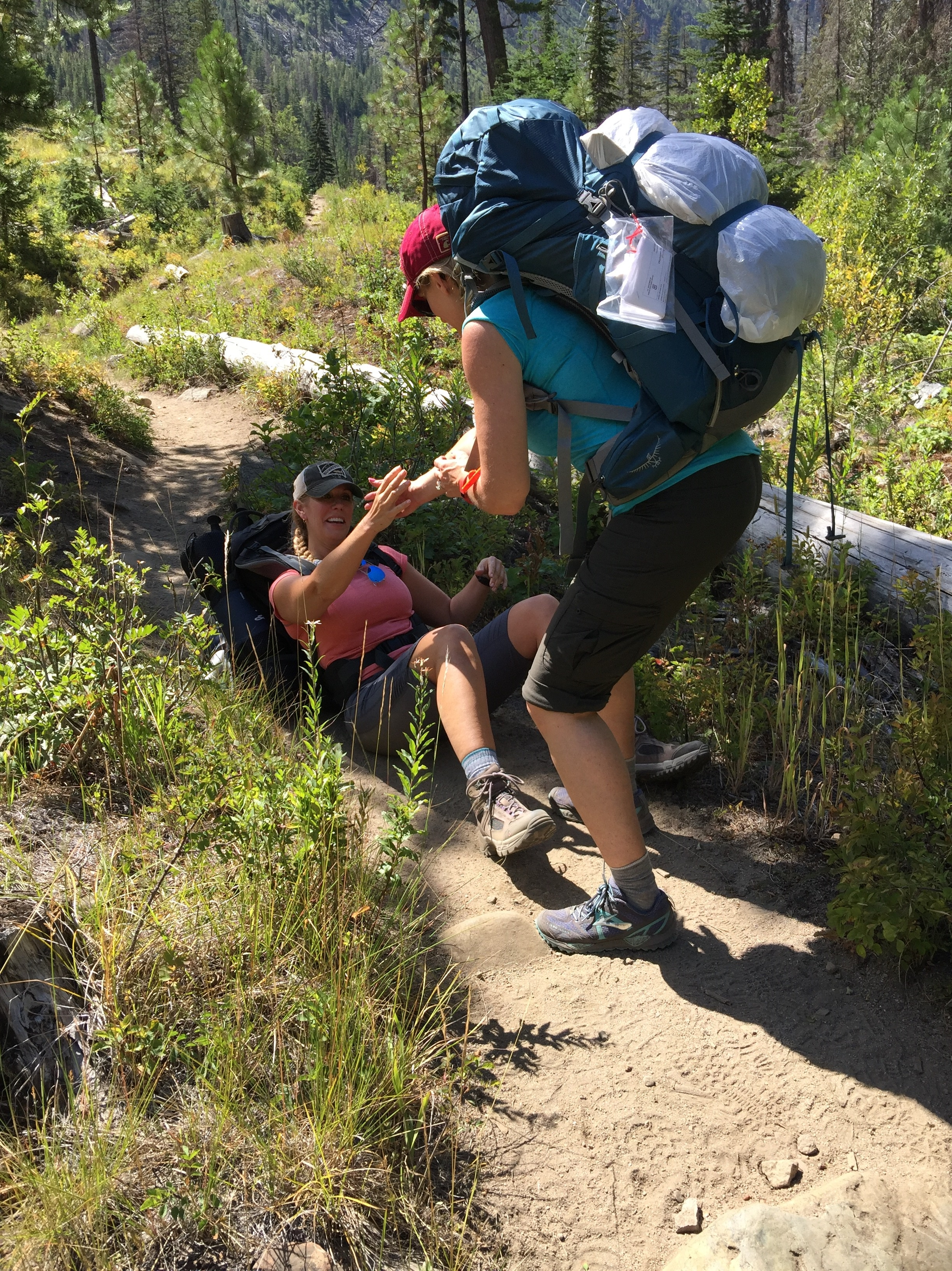 Girl falling on hike and getting a helping hand up