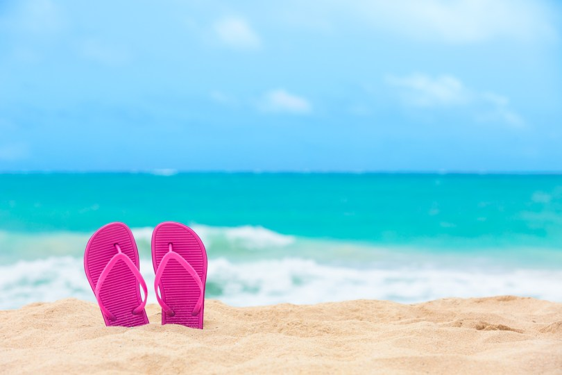 Pair of colorful slippers on the beach.