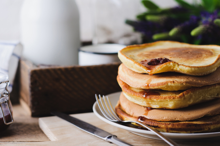 Pancakes and jam on an old wooden table. A still life with lupines and ware