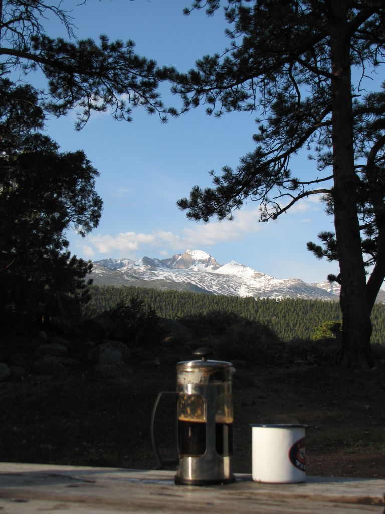 A  french press and coffee cup sit before a gorgeous mountain vista, inviting contemplation.